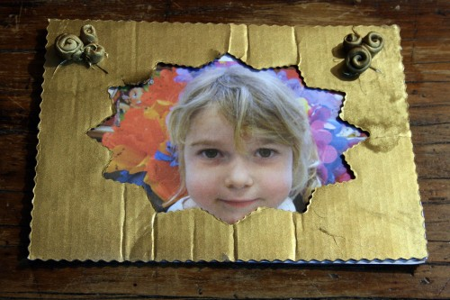 She made the frame with cardboard and flowers from clay and sprayed the whole thing gold